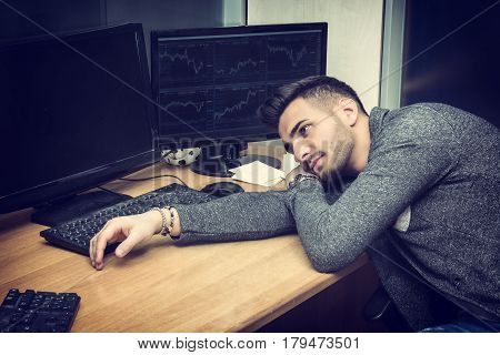 Tired bored sleepy young businessman or office worker sitting at his desk in front of his computer with his chin resting on his arm