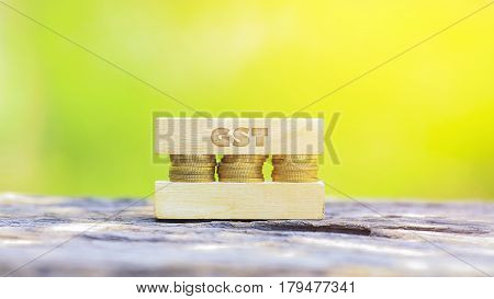 Business Concept - Gst Word, Golden Coin Stacked With Wooden Bar On Shallow Dof Green Background
