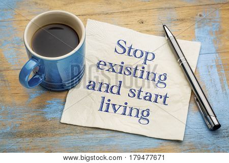 Stop existing and start living - handwriting on a napkin with a cup of espresso coffee