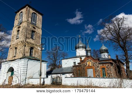 Orthodox Christian church next to the bell tower. Ancient buildings against a blue sky with white clouds. Sunny spring day. Deepest feeling of peace and tranquility.