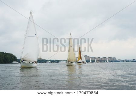 Sailing, yachting. Walk on a sailing yacht on the pond, the lake, on a cloudy summer day. Several large white sailing boat during the boat ride, or regatta. Summer vacation on the beach.