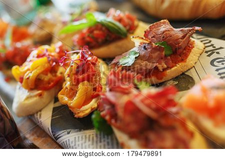 Classic Spanish tapas cooked for the visitors of the event on a wooden board in the restaurant. Bright delicious tapas catering service a delicious meal.