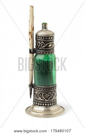 Traditional Moroccan green bottle with black kohl on white background