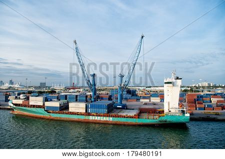 Miami Florida USA - March 18 2016: big cargo ship or barge with many shipping container in bay with lifting crane on Atlantic ocean water and cloudy blue sky sunny summer. traveling and vacation