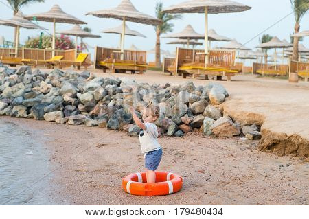 small baby boy or cute child with adorable face and blonde hair in shirt and shorts barefoot playing with red safety belt or lifebelt at sandy beach with stones umbrellas on natural background