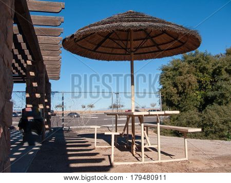 Shady combo of outdoor umbrella and wooden pergola to protect from scorching Arizona sun even in Winter
