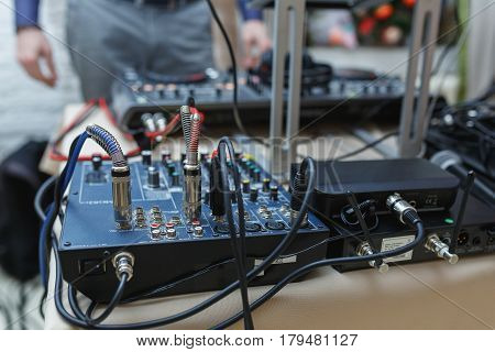 DJ mixer for sound effects and acoustic systems connection. Connected audio cables to a special sound console. Tools DJ and musicians.