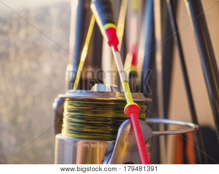 The bright float fishing rod and fishing reel close-up