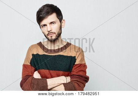 Studio portrait of young bearded hipster male looking upset indifferent shameful and Impolite. Dressed in oldfashioned colorful sweater guy crosses arms and stares in displeasure.