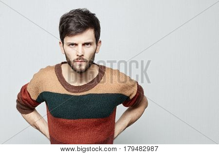 Portrait of young bearded Caucasian agressive male who looks forward in anger and threatens. Clenched teeth and menacing look make feel horrible. Human emotion concept.