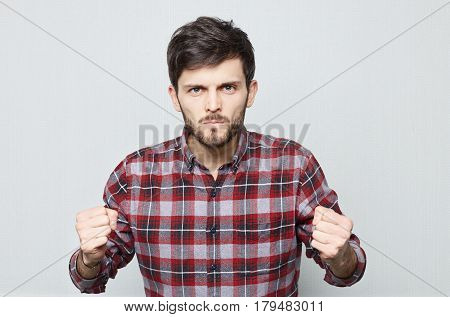 Studio close up of Caucasian male who holds his fists in anger and threatens. Bearded hipster guy in casual shirt looking forward сlenching cheekbones and ready to fight. Human emotions.
