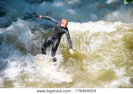 Boarders Surfing On The Isar River In Munich, Bayern, Germany