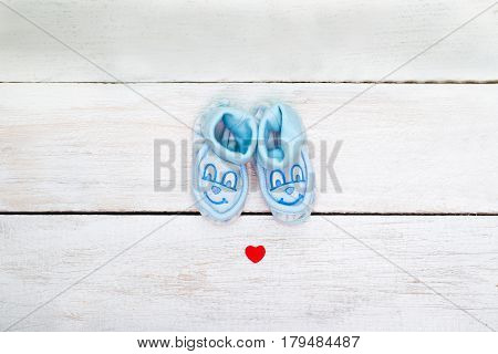 Blue booties for the boy on a white wooden background. view from above
