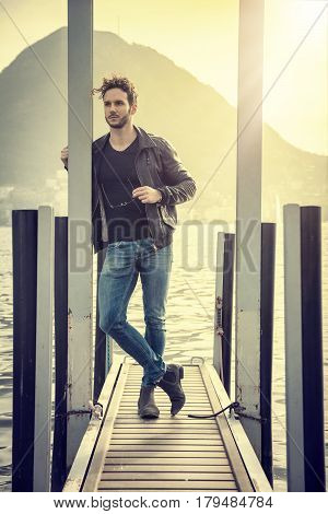 Handsome young man on a lake's shore in a sunny, peaceful day, standing