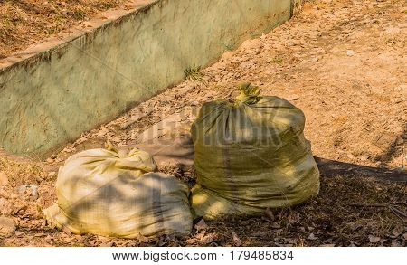 Two burlap bags of trash sitting in the shade of a tree next to a concrete wall
