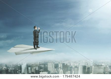 Businessman flying above a city with a big paper plane and yelling at the sky