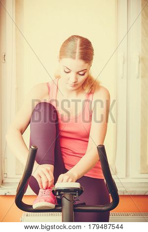 Woman On Exercise Bike Tying Lacing Shoes.