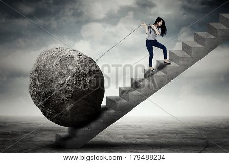 Image of beautiful female entrepreneur carrying big stone with a chain on the stair