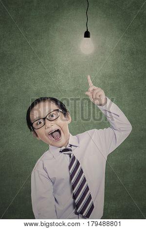 Business kid has bright idea under lit bulb in class