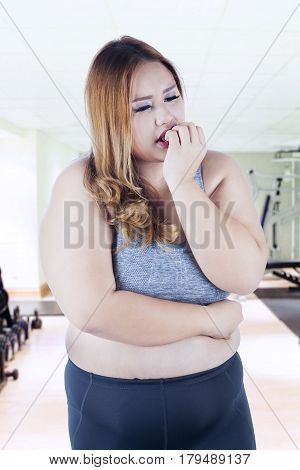Portrait of overweight woman looks nervous and biting nails in the fitness center