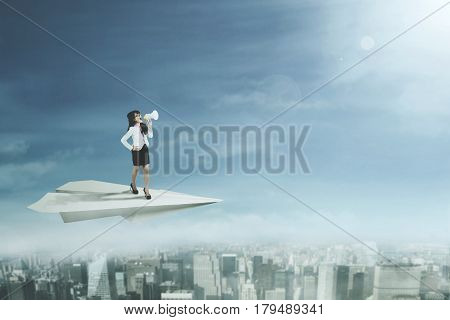 Female entrepreneur standing on a paper plane and yelling through a megaphone while flying above a city