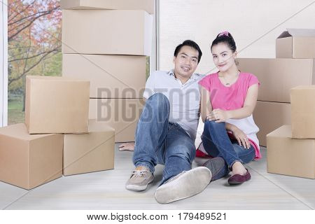 Picture of young Asian couple looking at the camera while sitting on floor after moving into a new house