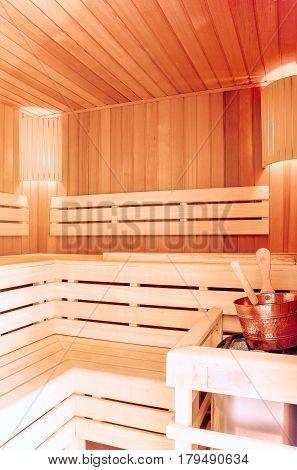 Sauna room. Wooden sauna interior with copper bucket. Bath accessories. Finnish sauna of small size.
