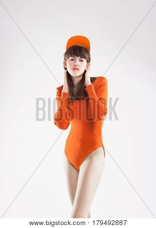 Fashion model with dark hair in an orange body and a cap on a light background. Creative fashion photo. Geometric poses. Creative makeup. Model with a bang and big ears.