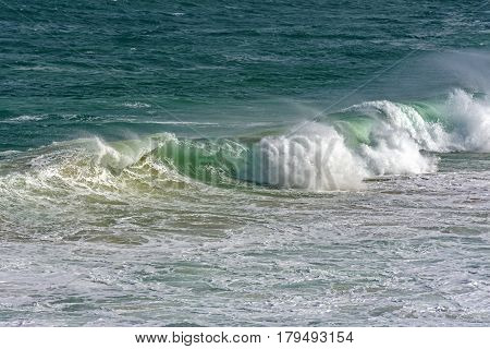 Wave crashing against rocks on the beach