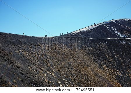tourists are walking on the ridge of one of the hundreds craters in the Etna Park - Sicily