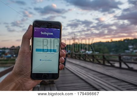 CHIANG MAI THAILAND - FEB 04 2017: A man hand holding iphone with login screen of instagram application. Instagram is largest and most popular photograph social networking.