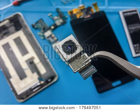 Close-up image of rear camera module on blurred smartphone component background