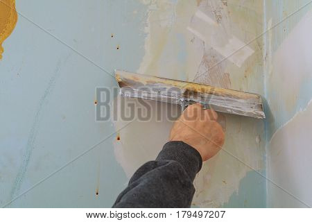 master makes repairs in the apartment and lining the walls with putty wall putty to defective