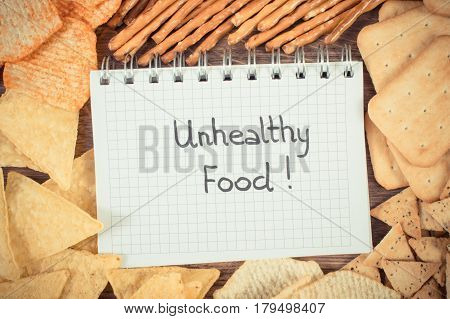 Vintage Photo, Inscription Unhealthy Food In Notebook And Heap Of Crisps And Cookies