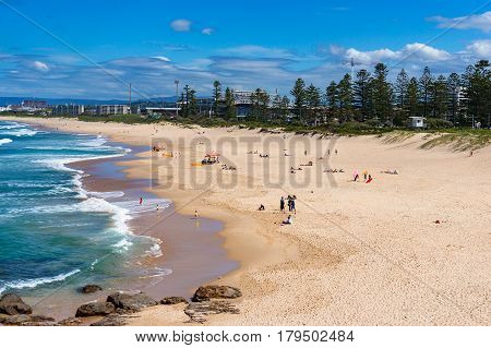 Aerial view of Wollongong beach with unrecognisable people relaxing and sunbathing under the summer sun
