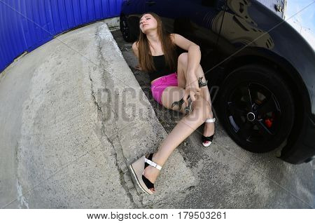 Girl In Pink Shorts With Wrenches Near A Black Car With An Open Hood