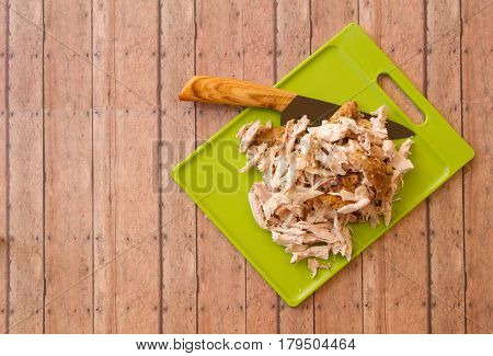 Shredded Rotisserie Chicken On A Green Cutting Board And Carving Knife Against Wood Plank Background