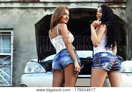 Two Young And Sexy Girls With Wheel Wrenches Around A Silvery Car With An Open Hood