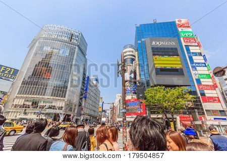 TOKYO, JAPAN - APRIL 19, 2014: Shibuya is famous for its scramble crossing and shopping district. It stops vehicles in all directions to allow pedestrians to inundate the entire intersection.