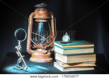 Still life in retro style on the dark background - books, kerosene lamp clock and magnifying glass. Selective soft focus.