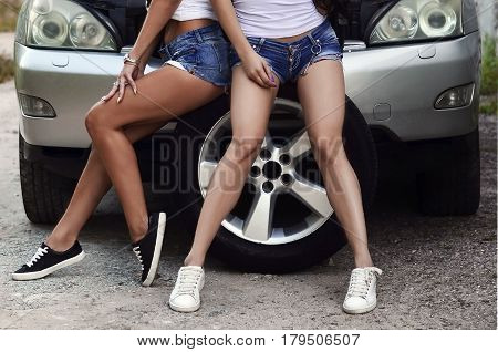 Some Fragments Of Bodies Of Two Young And Sexy Girls With Wheel Wrenches