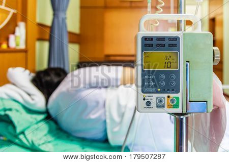Illness asian old woman lying on sickbed in hospital with infusion pump intravenous IV drip. Shallow depth of field IV machine in focus child out of focus. Health care and medical concept.