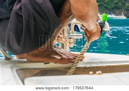 A young Man put down anchor to the sea and mooring rope tied around steel anchor on boat or ship