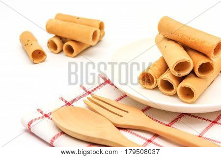 tong muan (a type of rolled wafer a traditional dessert in Thailand) with Cutlery Set on white plate over a white background