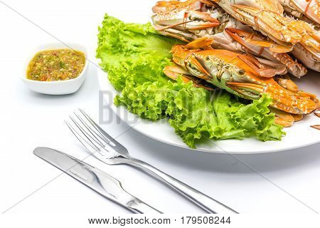 Steamed craps serve with Thai hot and spicy seafood sauce and Cutlery Set isolated on a white background Top view with copy space