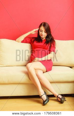 Pregnancy motherhood and happiness concept. Beautiful sexy stylish elegant pregnant woman in red dress relaxing on sofa and touching her belly