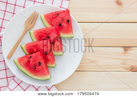 Watermelon slices on the white porcelain plate served with cutlery and napkin on a wooden background Top view with copy space for text.