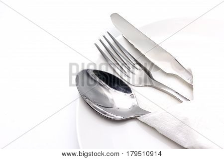 Knife spoon and fork with serviette over dish isolated on the white background with copy space for text.