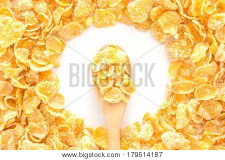 Pile of cornflakes and cornflakes on wooden spoon over white background Top view with copy space