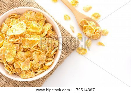 bowl of cornflakes and cornflakes on wooden spoon over a sackcloth on white table background Top view with copy space